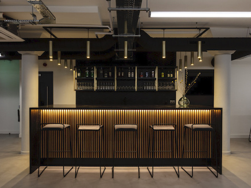 black painted bar in front of white painted walls and columns inside the Workstories office in London