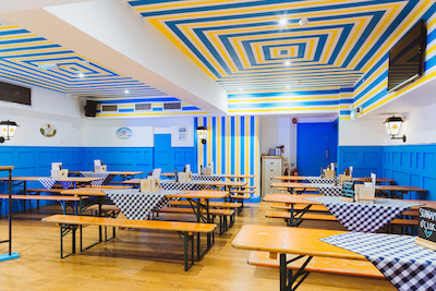 brand colours used in painted eating room with blue painted panelling and white painted walls and ceilings
