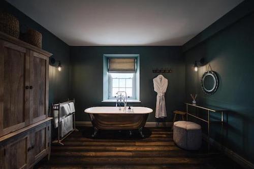 painted lounge area in Boult Wade officedark green painted bathroom with hardwood flooring