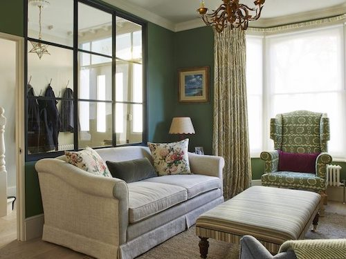fabric sofas in green painted living room in London