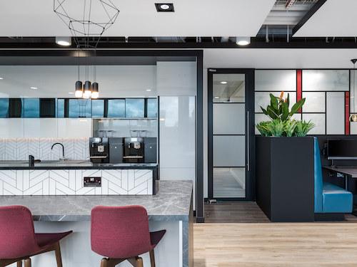 marble worktop and white ceramic tiled backsplash in office kitchen