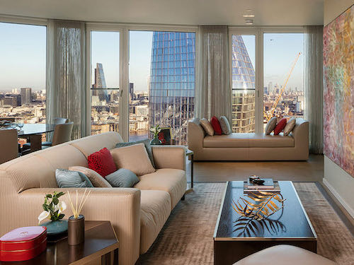 stylish furniture in cream painted living room looking out onto the London skyline