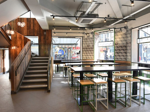 wooden chairs and tables in white painted dining room in Shake Shack