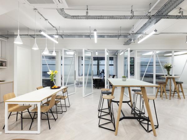 wooden shared desks inside white painted office in London